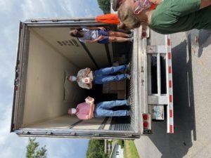Bill Skelton, Ethan Henderson, Elizabeth Moretz offloading milk from Borden Dairy truck