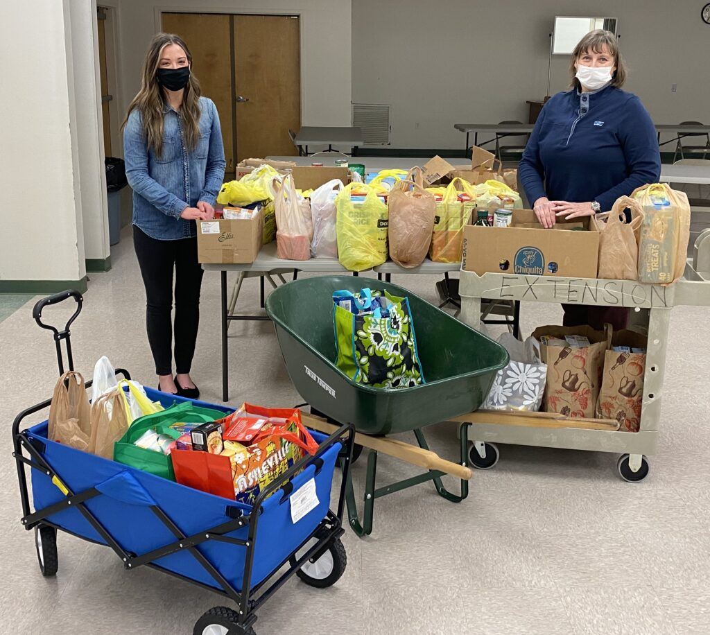 Social Worker and FCS agent standing with donated food.